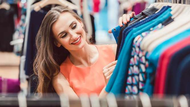 Woman browsing through dresses on rack in fashion store